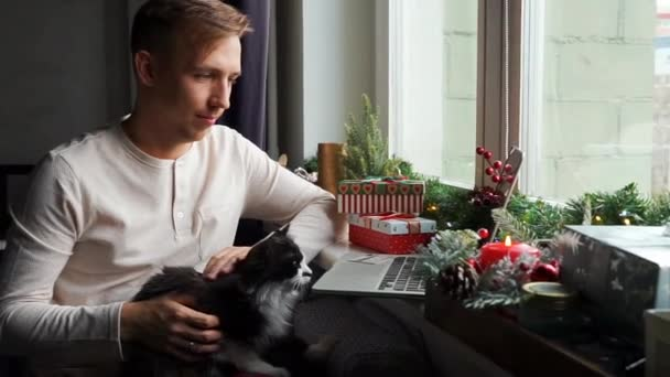 Young man freelancer in pajama working distance online having video call on laptop computer with cat at home office. Christmas mood, New Year decoration, xmas vacation. Lockdown isolation. Black cat.
