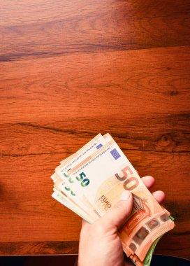 Ellerinde 50 avroluk banknotlar, ahşap masa arkası var. Avrupa Birliği 'nde maaş ve asgari ücret.