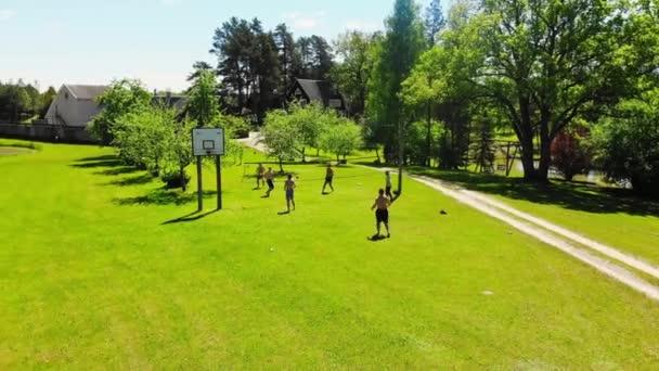 Letecký pohled skupina mladých bělošských přátel těšit hrát volejbal na travnaté ploše v Litvě venkova