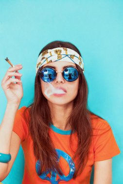 Boho girl portrait wearing blue sunglasses and smoking weed
