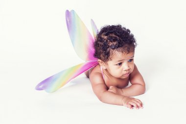 Lovely and thoughtful baby girl portrait wearing fairy wings
