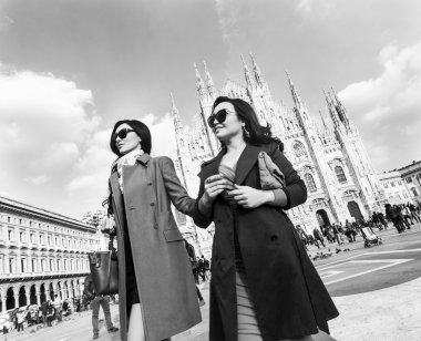 Beautiful and stylish women walking together in Milan monochrome