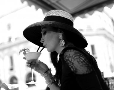 Beautiful vintage portrait of woman drinking cocktail black and