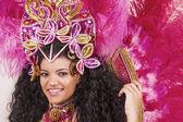 Krásný samba tanečnice nosí růžový kostým a usmívá se