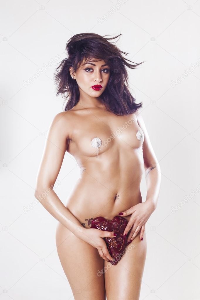 Gorgeous naked woman holding heart stone