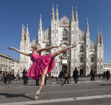Beautiful dancer wearing pink dress in Milan Cathedral Square