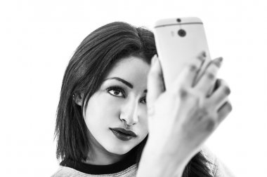 Beautiful woman smiling and taking a selfie black and white