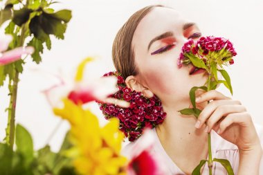 Woman portrait wearing and smelling flowers