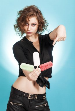 Beautiful girl holding and pointing out three popsicles