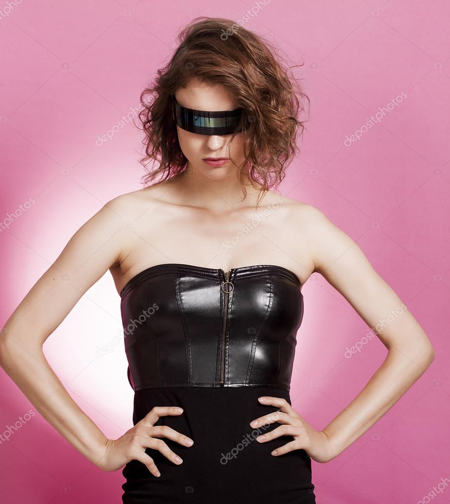 Sexy girl wearing futuristic sunglasses with hands on hips