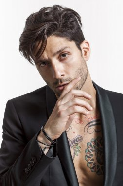 Sexy tattooed man closeup portrait wearing black jacket and look