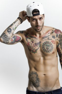 Handsome and sexy tattooed man portrait wearing baseball cap
