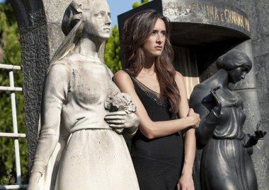 Woman portrait in grief between graveyard women statues
