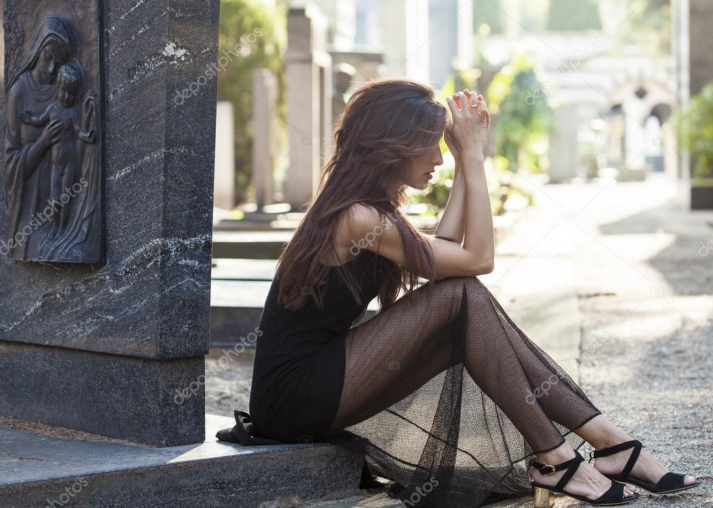 Sad woman portrait sitting in a graveyard