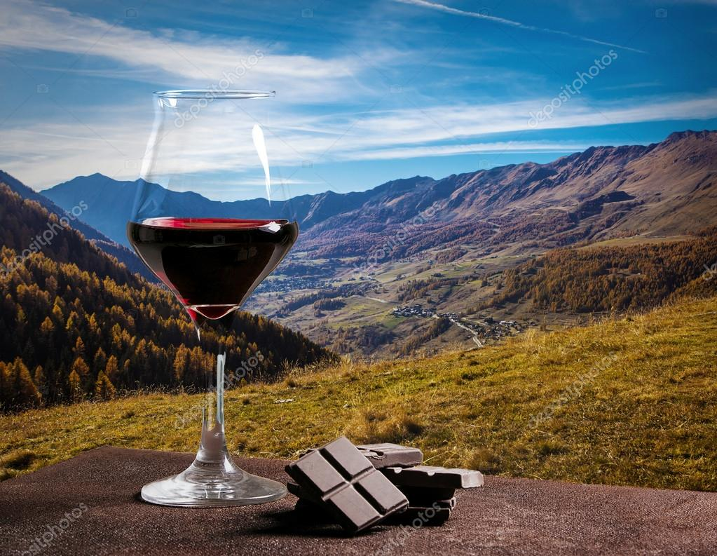 Red wine glass and chocolate with beautiful autumn landscape