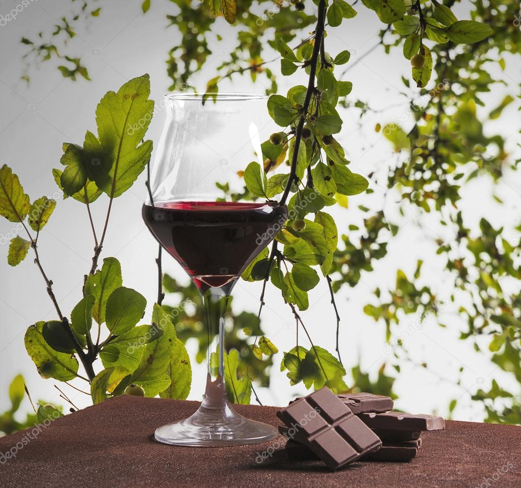 Red wine glass and chocolate with green leaves