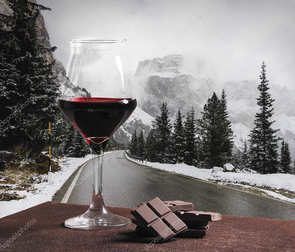 Red wine glass and chocolate with winter mountain road