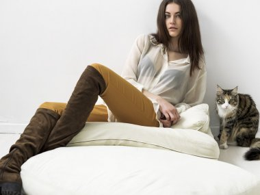 Pretty girl portrait sitting on cushions and looking and cat