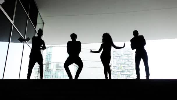 Group of dancers silhouettes performing in the city