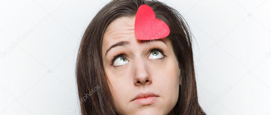 Sad girl looking at paper heart on her forehead letterbox