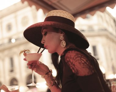 Beautiful vintage portrait of woman drinking cocktail