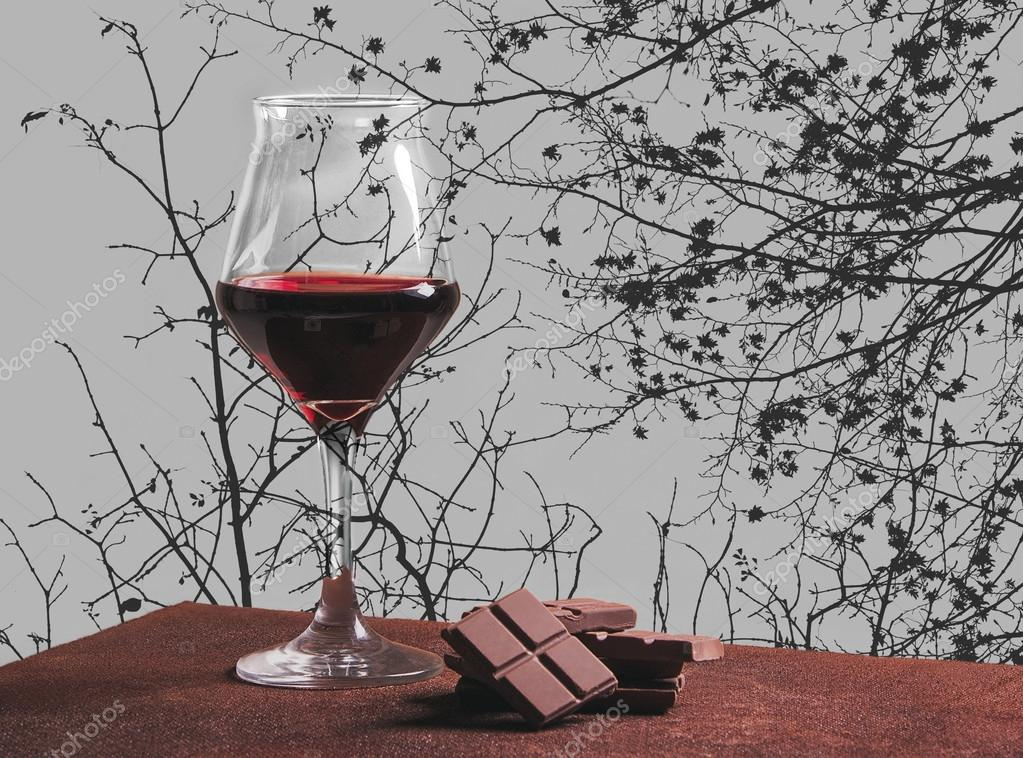 Red wine glass with chocolate and autumn tree branches