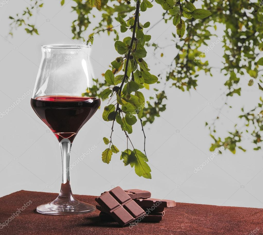 Red wine glass with chocolate and green leaves