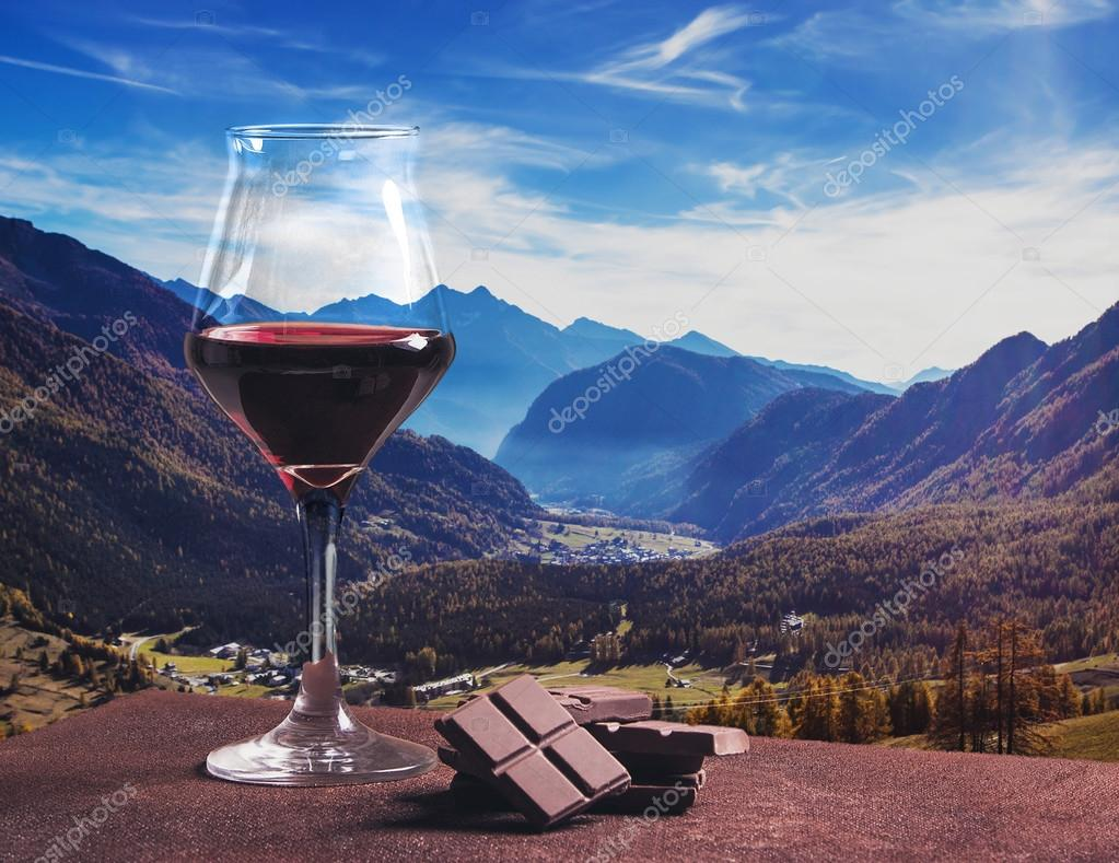 Red wine glass with chocolate and beautiful autumn mountainscape
