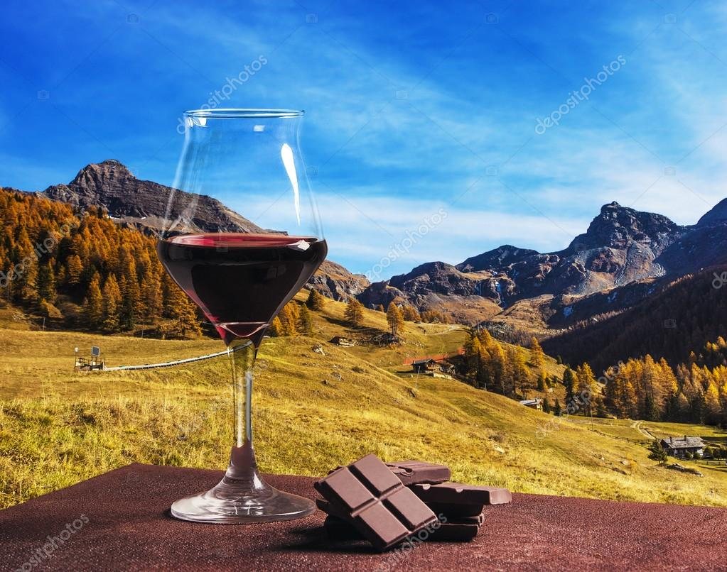 Wine glass with chocolate and beautiful autumn mountainscape