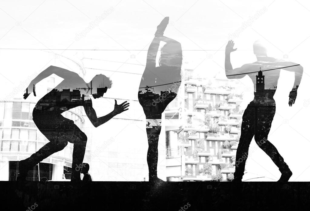 Double exposure of dancers silhouettes and city skyline monochro