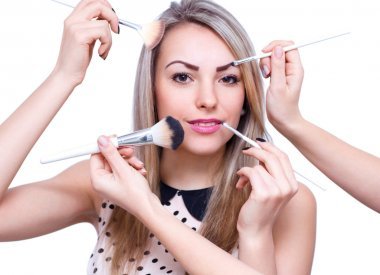 Make up woman with many hands. Makeup brushes. Isolated on whit
