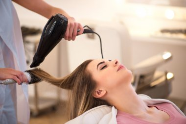 Professional hairdresser drying hair of her client