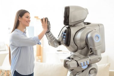 Positive  girl and robot giving high five