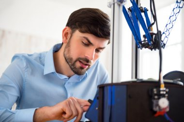 Pleasant man working with 3d printer