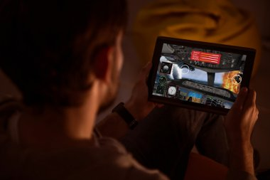 Guy holding a tablet and playing videogame