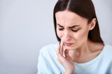 Cheerless woman having toothache