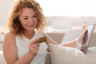 Pleasant woman holding credit card