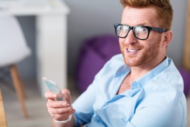 Joyful handsome man holding cell phone