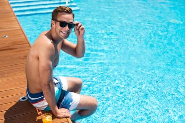 Positive delighted man sitting near swimming pool