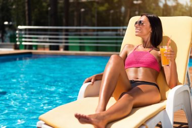Relaxed delighted woman resting near swimming pool