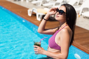 Delighted woman drinking cocktail