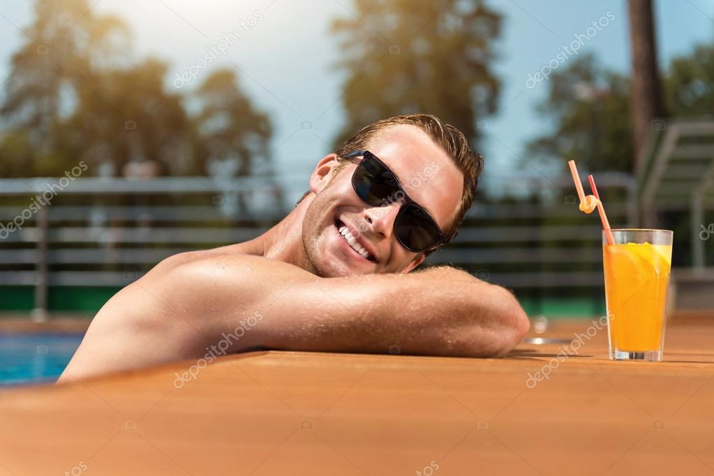 Positive smiling man relaxing in the swimming pool