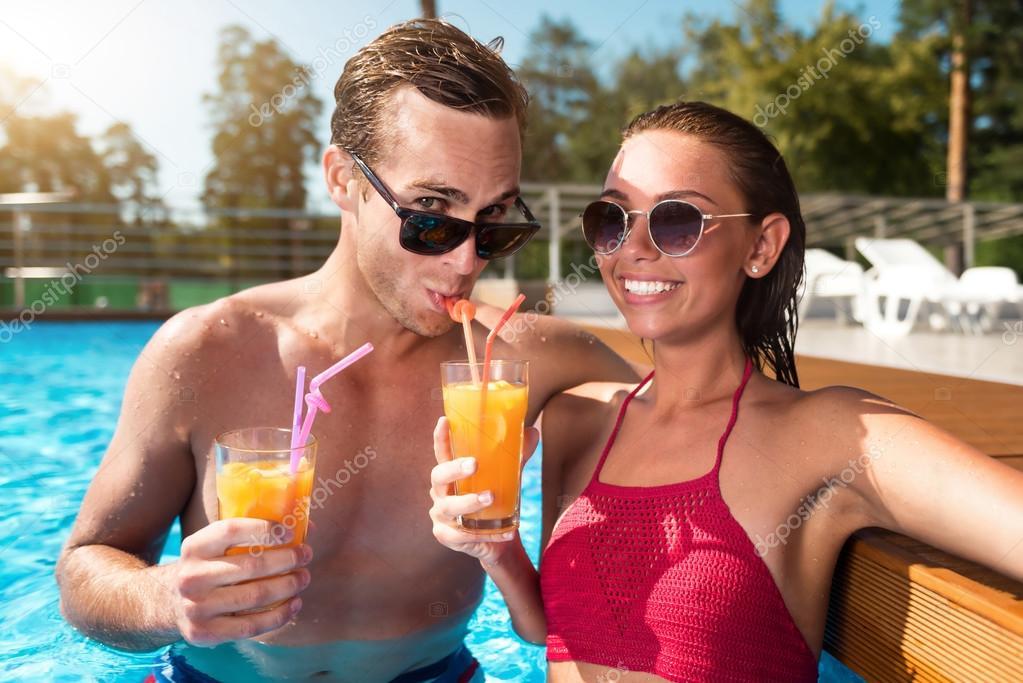 Positive couple drinking cocktails in a swimming pool