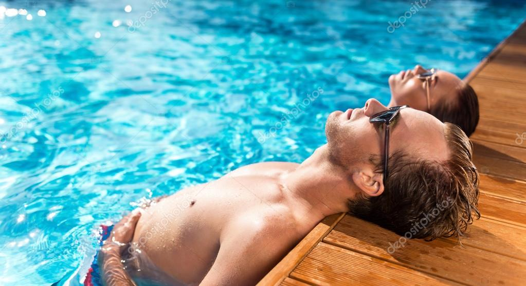 Pleasant delighted couple resting in the swimming pool