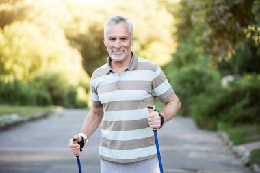 Active senior citizen jogging in the park with tracksticks