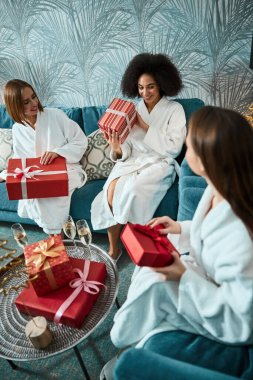 Three inspired young ladies exchanging Christmas gifts in cozy room