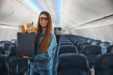 Joyful lady on a plane presenting shopping bag with gifts