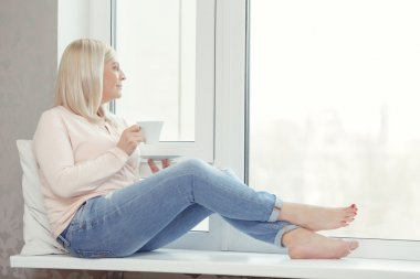 Woman sits on the windowsill