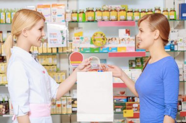 Pharmacy chemist and customer at the drugstore