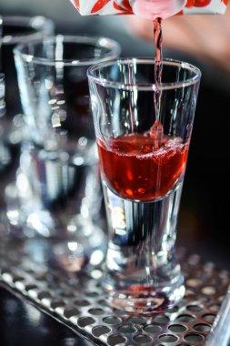Barman makes shots in a bar